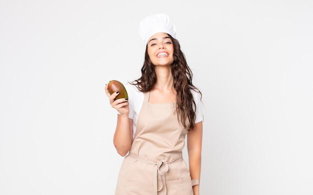 Красивая женщина выглядит счастливой и приятно удивленной в фартуке и держит манго