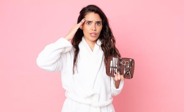 Красивая женщина выглядит счастливой, удивленной и удивленной и держит сумку для макияжа с инструментами для ногтей