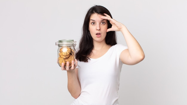 Pretty woman looking happy, astonished and surprised and holding a cookies glass bottle