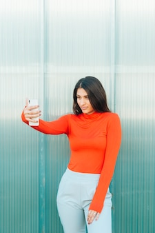 Pretty woman looking at mobile phone screen standing against wall