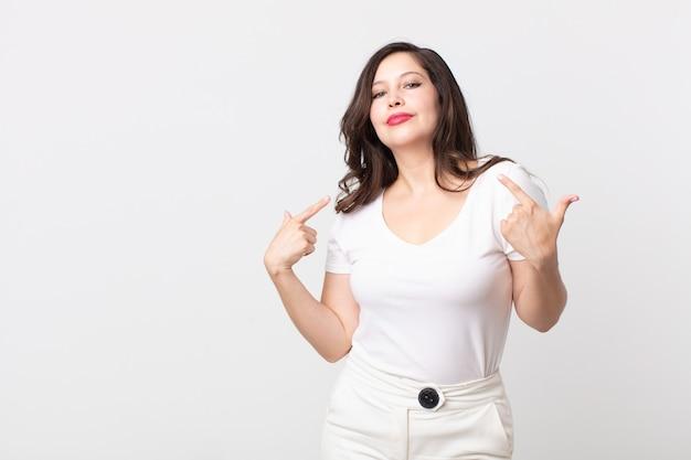誇らしげに、傲慢で、幸せで、驚き、満足しているように見え、自己を指して、勝者のように感じているきれいな女性