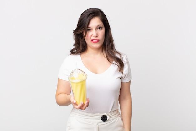 困惑して混乱しているように見え、バニラミルクセーキを持っているきれいな女性