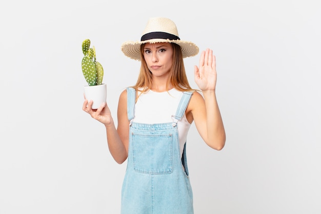 開いた手のひらを見せて停止ジェスチャーをし、サボテンの観葉植物を持っている真剣な表情のきれいな女性