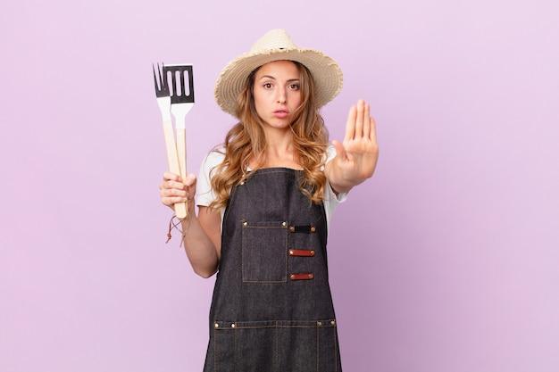 Симпатичная женщина, выглядящая серьезной, показывая открытую ладонь, делая стоп-жест. концепция шеф-повара барбекю