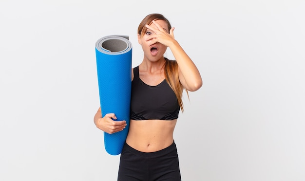 Pretty woman looking shocked, scared or terrified, covering face with hand. yoga concept