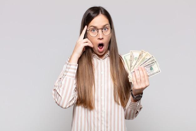 Pretty woman  looking surprised holding bills