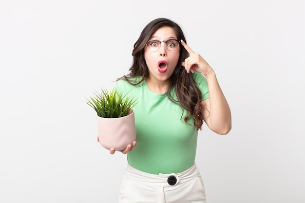 Красивая женщина выглядит удивленной, осознает новую мысль, идею или концепцию и держит декоративное растение