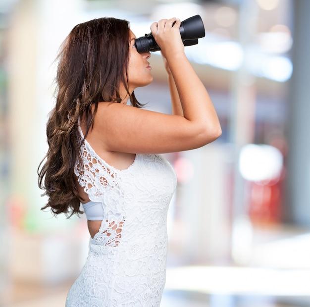 Pretty woman looking through binoculars