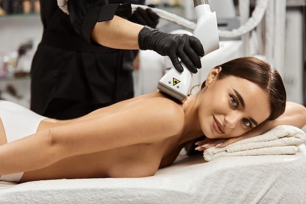 Красивая женщина смотрит в камеру и получает массаж плеч
