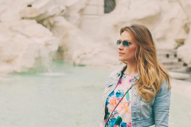 Красивая женщина, глядя на фонтан треви