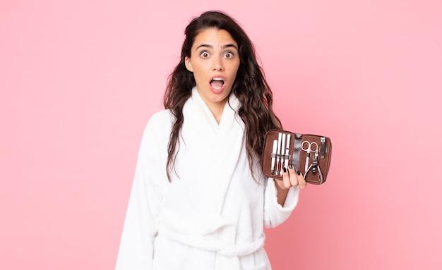 Красивая женщина выглядит очень шокированной или удивленной и держит сумку для макияжа с инструментами для ногтей