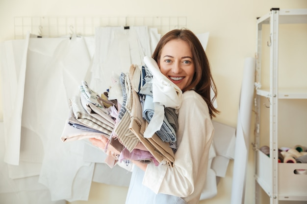 Pretty woman looking while holding pile of fabrics
