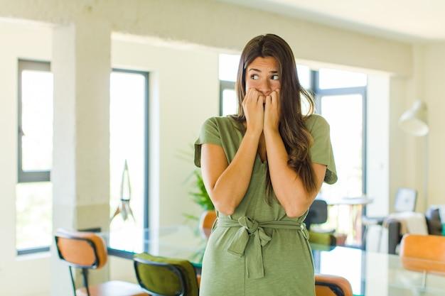 Красивая женщина выглядит встревоженной, встревоженной, напряженной и напуганной, кусает ногти и смотрит в пространство для боковой копии