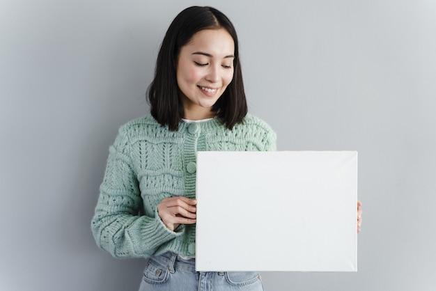 きれいな女性は彼女の手で一枚の紙を見る