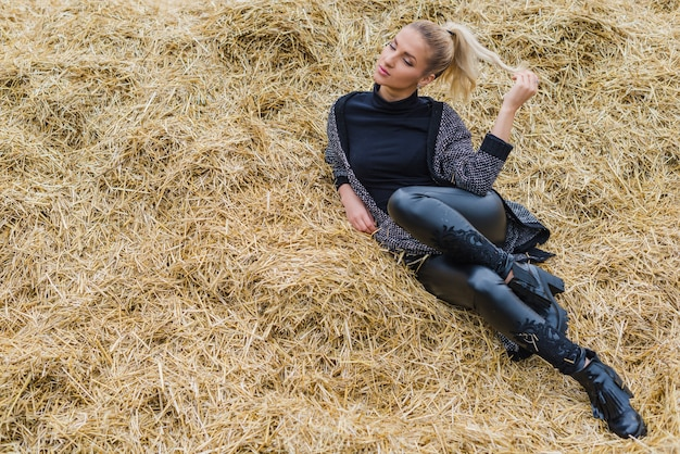 Pretty woman lying in hay