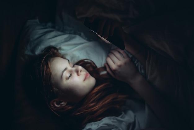 就寝前の中毒の前に電話で夜ベッドに横たわっているきれいな女性。