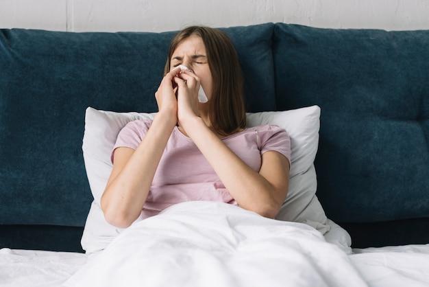 Красивая женщина, лежа на кровати, страдающая от холода