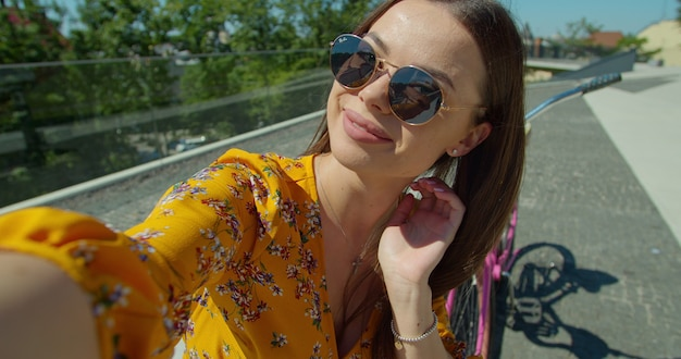 晴れた日に公園できれいな女性がビデオ通話をします。ベンチに座ってスマートフォンを使用してビデオ通話を行う若い女性。