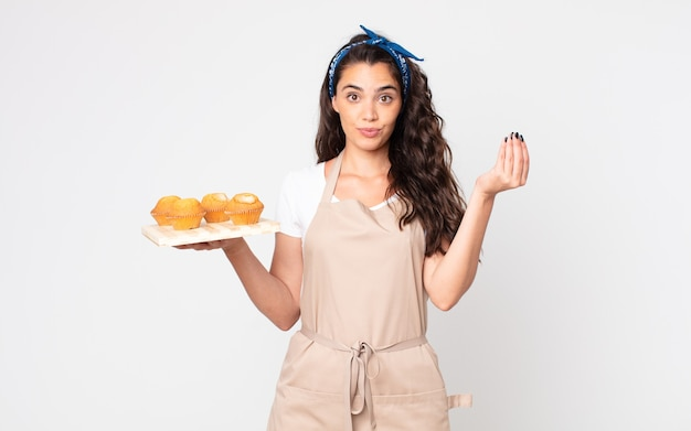 Pretty woman making capice or money gesture, telling you to pay and holding a muffins tray