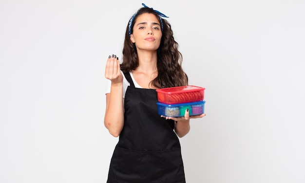 Pretty woman making capice or money gesture, telling you to pay and holding tupperwares with food