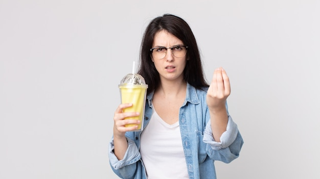 Pretty woman making capice or money gesture, telling you to pay and holding a vanilla milkshake