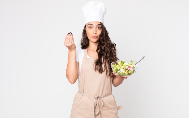 Pretty woman making capice or money gesture, telling you to pay wearing an apron and holding a salad