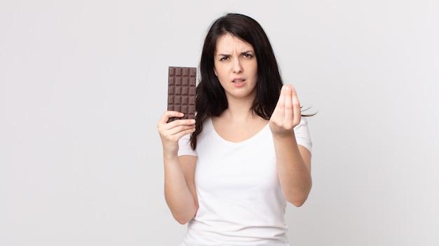 きれいな女性がcapiceまたはお金のジェスチャーをして、あなたに支払うように言って、チョコレートバーを持っています