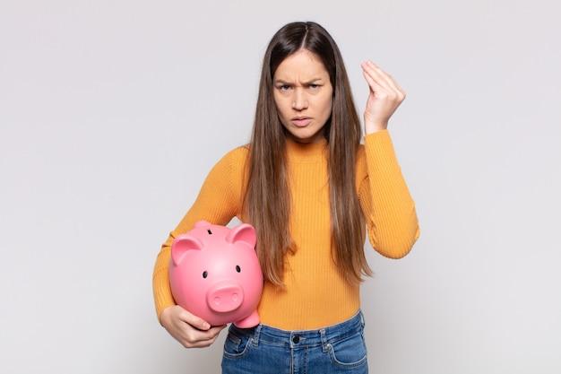 Красивая женщина делает капризный или денежный жест, говоря вам, чтобы вы заплатили свои долги!