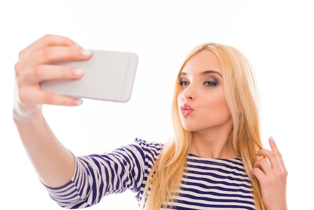 Красивая женщина делает селфи на своем смартфоне и надувается