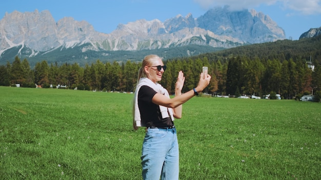 Pretty woman making video call from beautiful nature park in front of mountains. she sharing impressions from her trip.