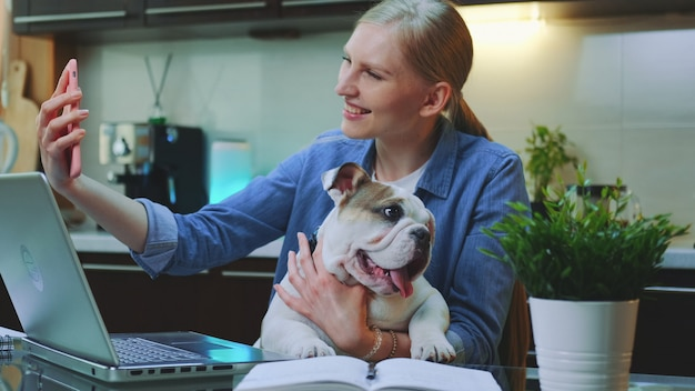 Pretty woman making video call on smartphone with a small dog on her hands