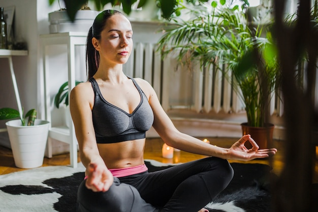 Pretty woman meditating at home
