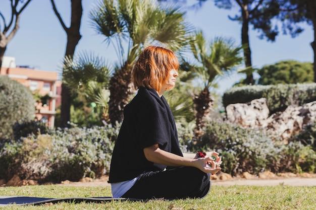公園で瞑想する美しい女性