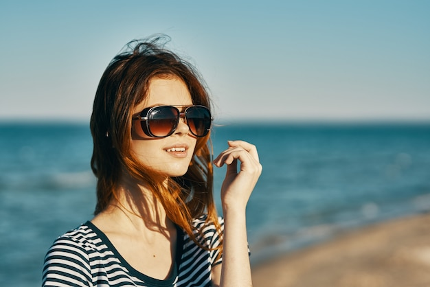 Pretty woman model in sunglasses by the sea in the mountains