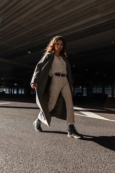 패션 긴 코트, 흰색 스웨터, 바지, 부츠에 곱슬 머리를 가진 예쁜 여자 모델은 화창한 날과 그림자에 거리를 걷습니다. 도시 여성의 스타일과 아름다움