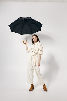 Pretty woman on modern fashionable suit brown boots umbrella over head