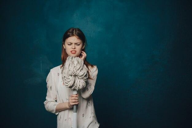 Красивая женщина шваброй в руке убирая удовольствие по уходу за домом
