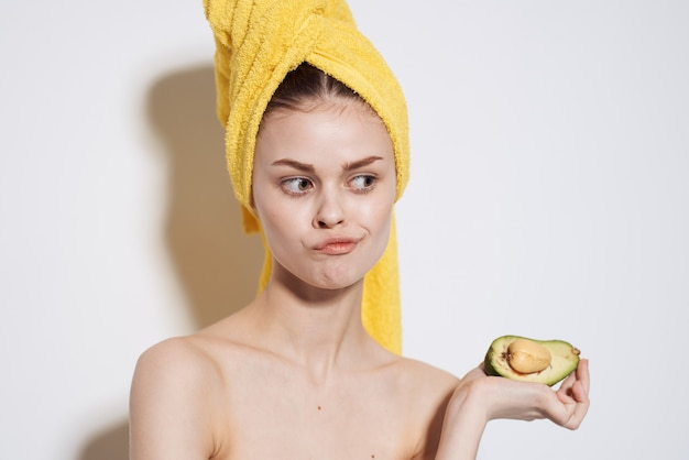 Красивая женщина голые плечи авокадо экзотические фрукты косметика чистая кожа