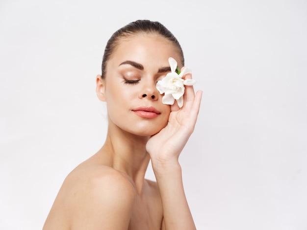 きれいな女性の裸の肩は目を閉じた白い花孤立した背景
