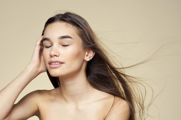 きれいな女性の裸の肩の化粧品きれいな肌のヘアケアベージュ。