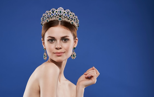 Pretty woman naked shoulders crown on head decoration makeup blue background