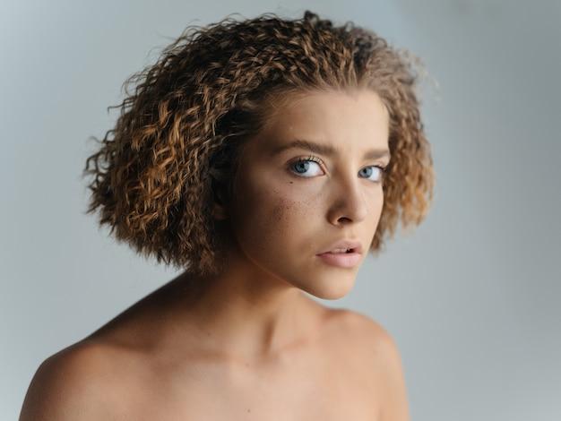 きれいな女性の裸の肩の巻き毛のクローズアップ