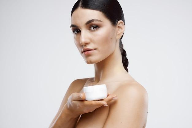 きれいな女性の裸の肩はスキンケア明るい背景に直面しています
