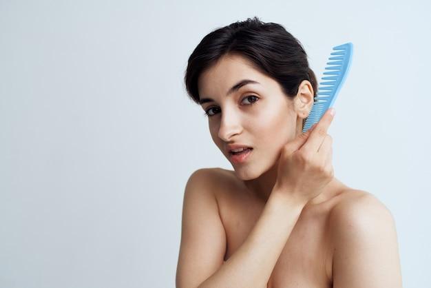 きれいな女性の裸の肩のヘアブラシのヘアケアクロップドビュー。