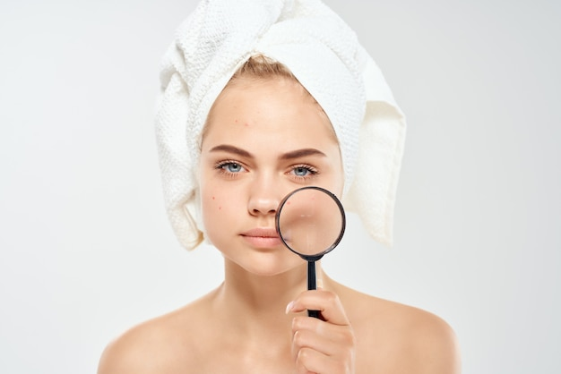 Pretty woman naked shoulders magnifier near face dermatology skin care