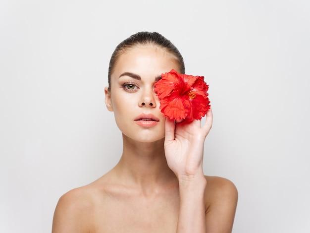 きれいな女性の裸の肩の赤い花の近くの顔の化粧品のトリミングされたビュー