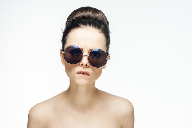 Pretty woman naked shoulders sunglasses glamor light.