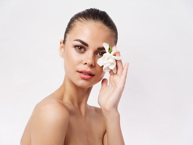 きれいな女性の裸の肩の白い花の顔の化粧品の近く