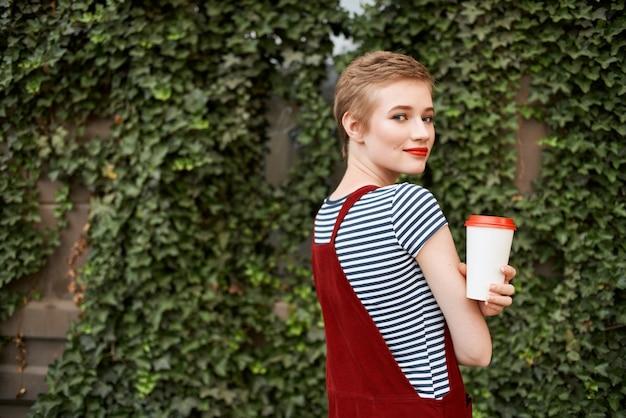 屋外の茂みの近くのきれいな女性は飲み物と一緒にカップを歩く