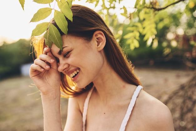 木の近くのきれいな女性は、魅力的な家のクローズアップを残します